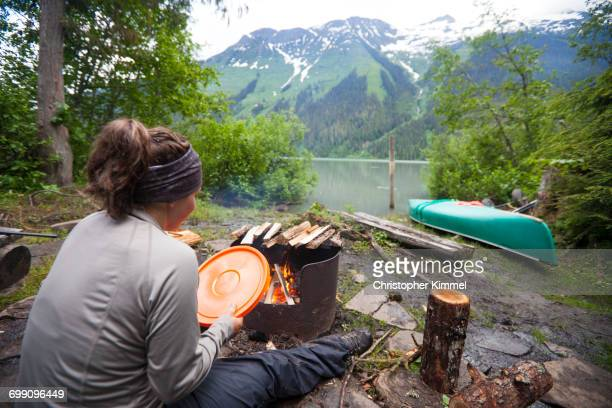 A woman uses a bucket lid to fan a fire while camping beside Lanezi Lake in Bowron Lake Provincial Park.