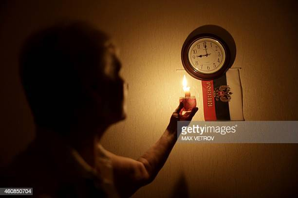 A woman uses a candle to look at a clock during a power outage in the Crimean city of Simferopol on December 26 2014 Crimea on December 24 and...
