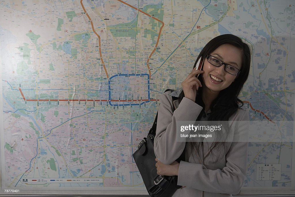 Subway Map Phone.A Woman Uses A Cell Phone Beside A Subway Map Stock Photo Getty Images