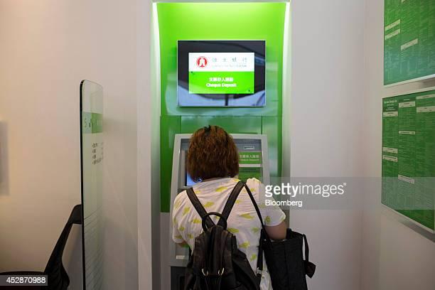 A woman uses a cheque deposit machine at a Hang Seng Bank Ltd branch in Hong Kong China on Wednesday July 23 2014 Hang Seng Bank majorityowned by...