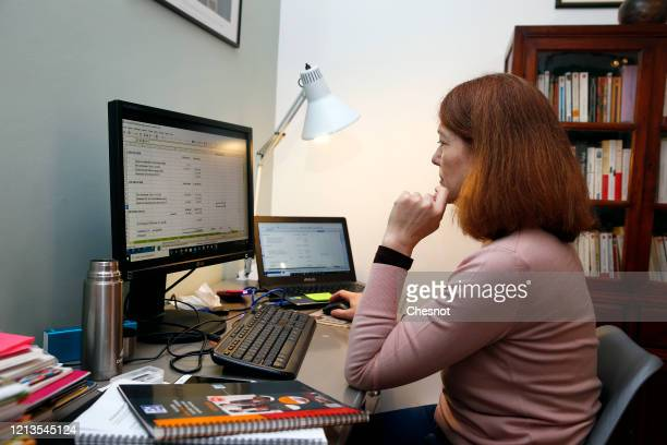 A woman uses a computer to work from her home on the third day after the announcement by French President Emmanuel Macron of the confinement of the...