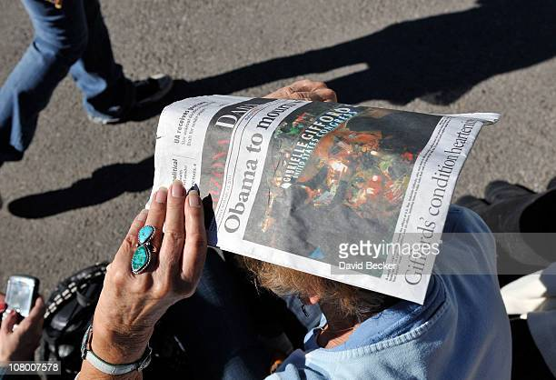 A woman uses a copy of the Arizona Daily Wildcat to shield her eyes as she waits in line for a memorial service honoring Saturday's shooting victims...