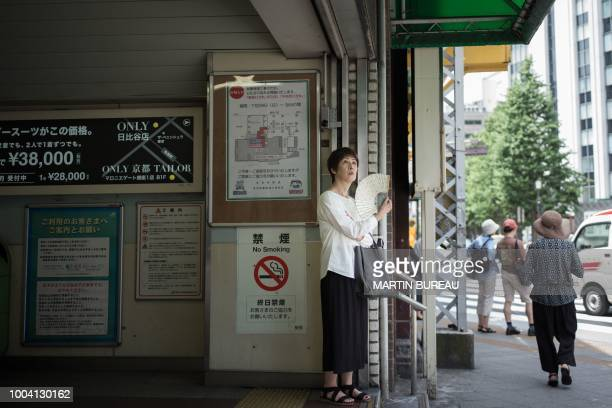 A woman uses a fan as she stands along a street in Tokyo on July 23 as Japan suffers from a heatwave Japan's severe heatwave killed at least 15...