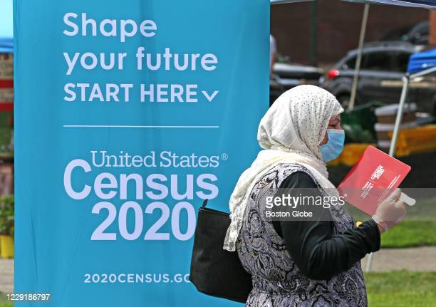 Woman uses a fan to cool off while waiting at a Census 2020 booth at a farmer's market in Everett, MA on July 24, 2020. Some communities are at risk...
