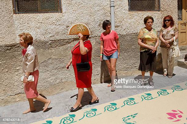 A woman uses a fan to cover from the sunshine as she walks next to a sawdust carpet during the Corpus Christi feast on June 7 2015 in Elche de la...