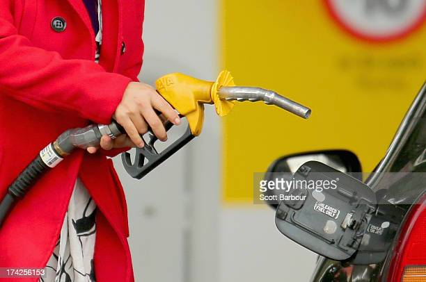A woman uses a fuel dispenser to fill her car up with petrol at a petrol station on July 23 2013 in Melbourne Australia According to CommSec fuel...
