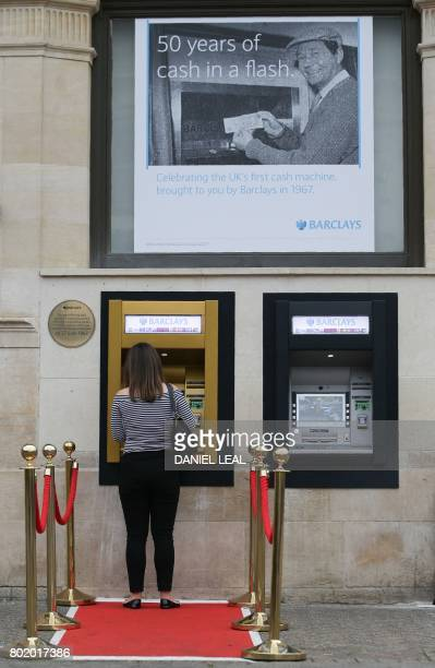 A woman uses a gold coloured automated teller machine outside a branch of British bank Barclays in Enfield north London on June 27 on he 50th...