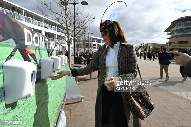 A woman uses a hand sanitiser on the final day of the Cheltenham Festival horse racing meeting at Cheltenham Racecourse in Gloucestershire southwest...