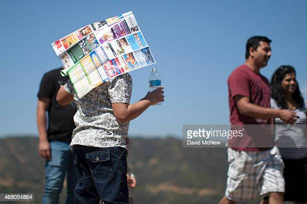A woman uses a Hollywood tourist map as makeshift sunshade in Griffith Park on March 29 2015 in Los Angeles California A recordbreaking series of...