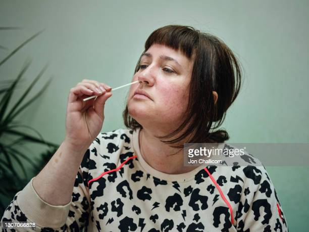 a woman uses a home self testing kit for covid-19 - medical examination stock pictures, royalty-free photos & images