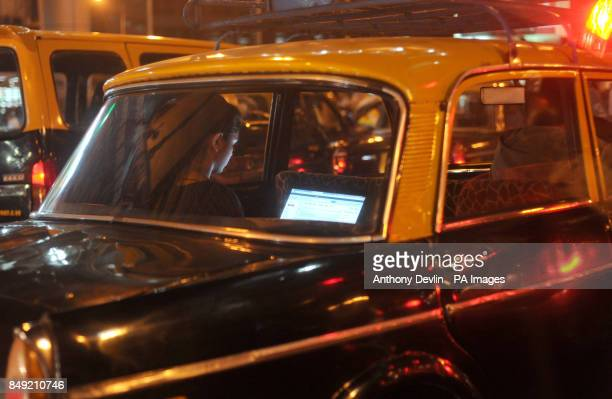 A woman uses a laptop in the back of a traditional taxi in Mumbai India