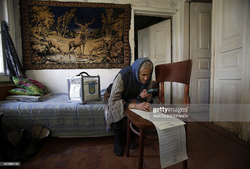 A woman uses a magnifying glass to read her ballot while voting at home in the village of Gornostaypol, some 80 km north of Kiev, on October 26, 2014, during Ukraine's parliamentary elections. Ukrainians voted in parliamentary elections on October 26 that could sharpen divisions in the war-torn country, while strengthening President Petro Poroshenko's bid to set the ex-Soviet republic on an irreversible pro-Western course.