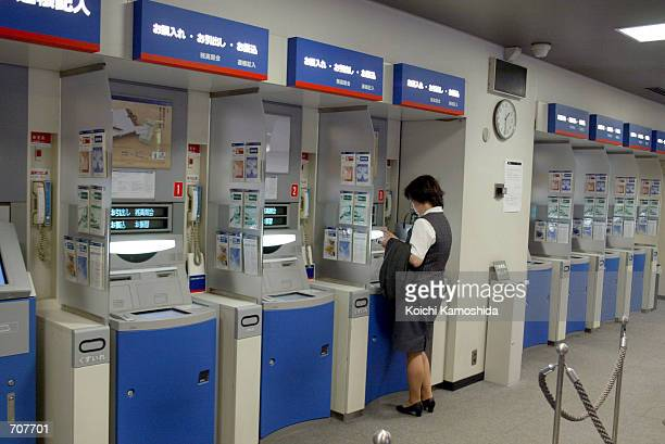 A woman uses a Mizuho Bank ATM April 16 2002 in Tokyo Mizuho Bank has fixed computer system glitches affecting its automatic teller machine network...