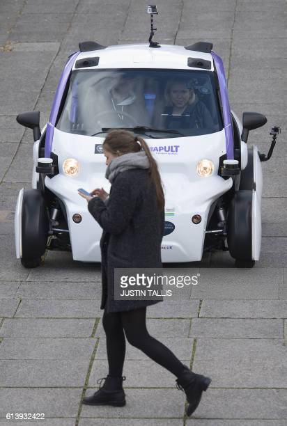 A woman uses a mobile phone as she walks in front of an autonomous selfdriving vehicle as it is tested in a pedestrianised zone during a media event...