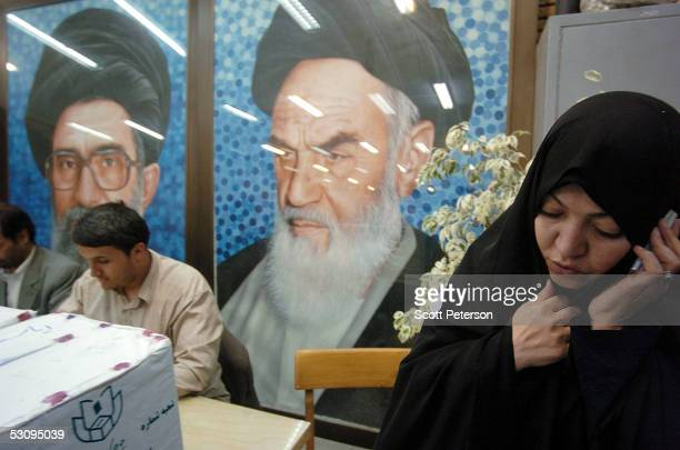 A woman uses a mobile phone near the ballot boxes set before a portrait of Iran's supreme leader Ali Khamenei and father of Iran's 1979 Islamic...