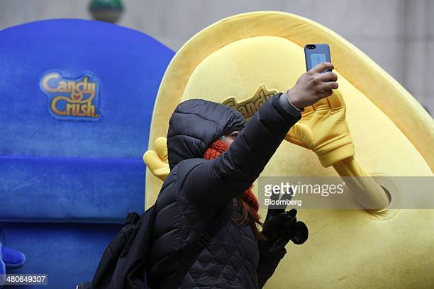 A woman uses a mobile phone to take a selfie with characters from King Digital Entertainment Plc's Candy Crush game in front of the New York Stock...