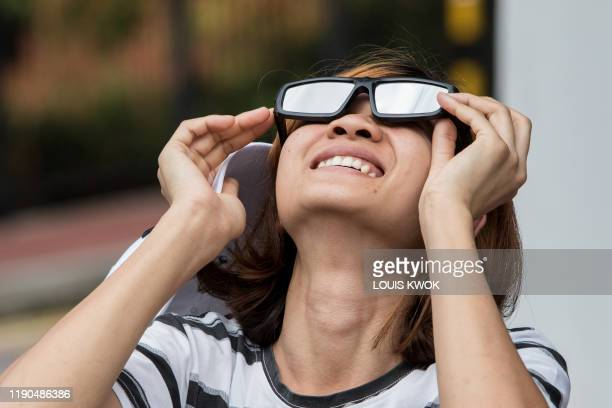 A woman uses a pair of solar filter glasses to watch as the moon moves in front of the sun in a rare ring of fire solar eclipse in Singapore on...