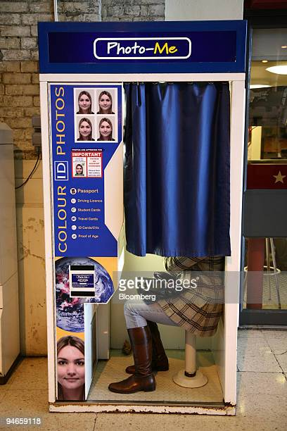 A woman uses a PhotoMe photo booth in Victoria Station London UK on Thursday Nov 29 2007 PhotoMe International Plc the UK operator of 25000 photo...