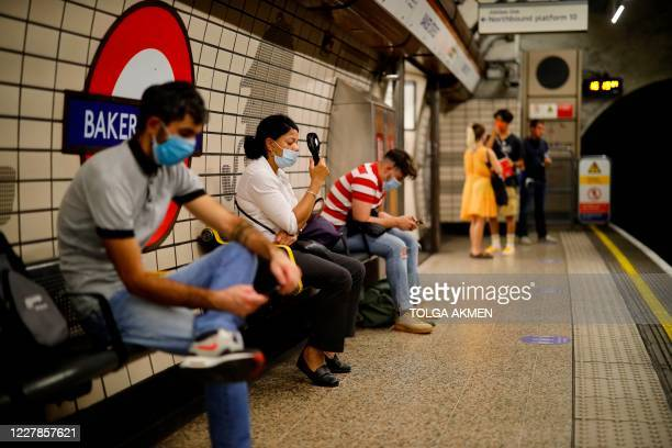 A woman uses a portable fan to cool down on a London Underground station platform in the warm weather in London on July 31 2020 A storm warning...
