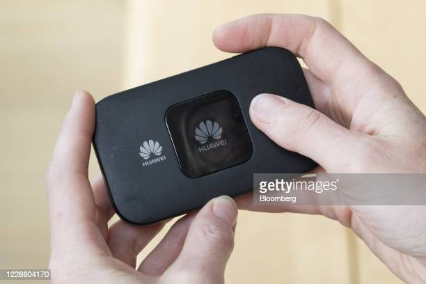 A woman uses a portable mobile WiFi hotspot device produced by Huawei Technologies Co in this arranged photograph in Shalford UK on Monday July 13...
