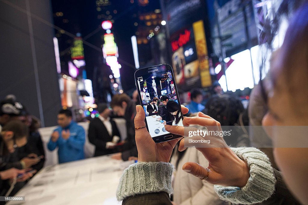 A woman uses a Samsung Electronics Co. Galaxy S4 smartphone to take a photograph during the Galaxy S4's release in Times Square in New York, U.S., on Thursday, March 14, 2013. Samsung Electronics Co. unveiled the Galaxy S4 with a bigger screen and software that tracks eye movements as the world's biggest smartphone seller takes its battle with Apple Inc. to the iPhone maker's home market. Photographer: Michael Nagle/Bloomberg via Getty Images