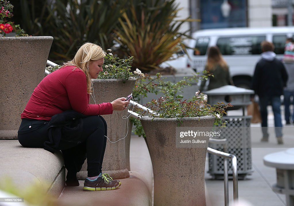 A woman uses a smartphone as she sits in Union Square on June 5, 2013 in San Francisco, California. According to a study by the Pew Internet & American Life Project, over half of American adults, or 56 percent, have smartphones, up from 35 percent two years ago.