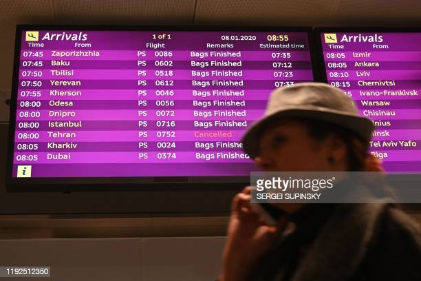 TOPSHOT A woman uses a smartphone as she walks past an arrivals board displaying the Ukraine International Airlines Flight PS752 from Tehran marked...