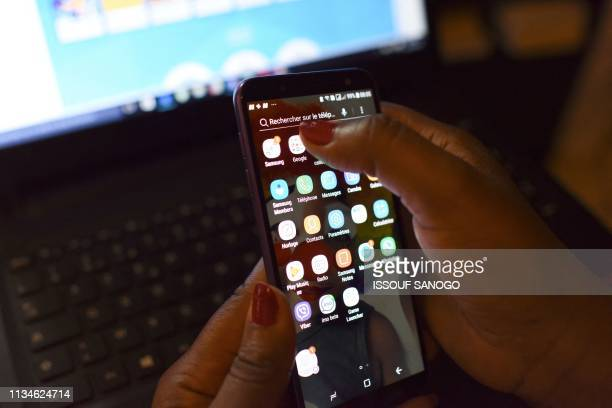 A woman uses a smartphone in front of a laptop on April 3 in Abidjan According to the figures of the platform of the fight against cybercrime of the...