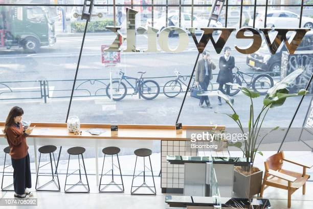 Woman uses a smartphone in the reception area of the WeWork Cos. Iceberg co-working space in Tokyo, Japan, on Thursday, Dec. 20, 2018. The...