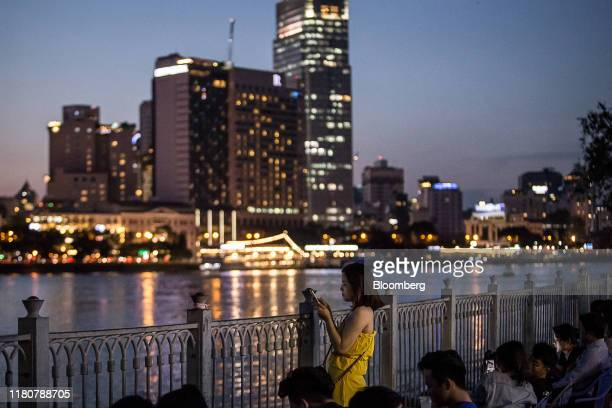 A woman uses a smartphone while standing along the Saigon River in Ho Chi Minh city Vietnam on Wednesday Sept 11 2019 Vietnam is the seventhlargest...