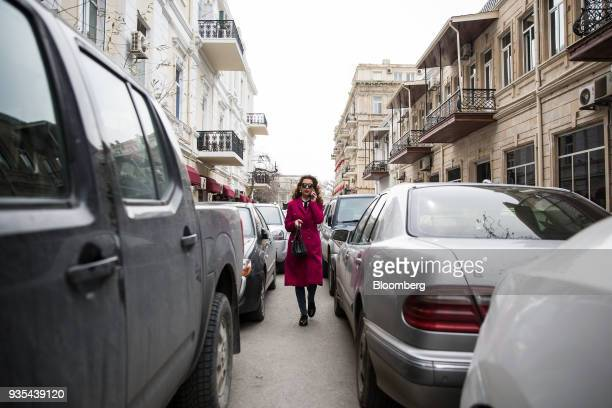 A woman uses a smartphone while walking between rows of cars in Baku Azerbaijan on Friday March 16 2018 Azerbaijan's economy barely returned to...