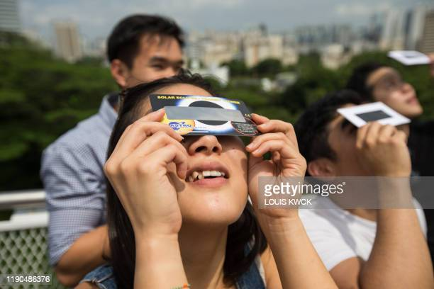 A woman uses a solar filter to watch as the moon moves in front of the sun in a rare ring of fire solar eclipse in Singapore on December 26 2019