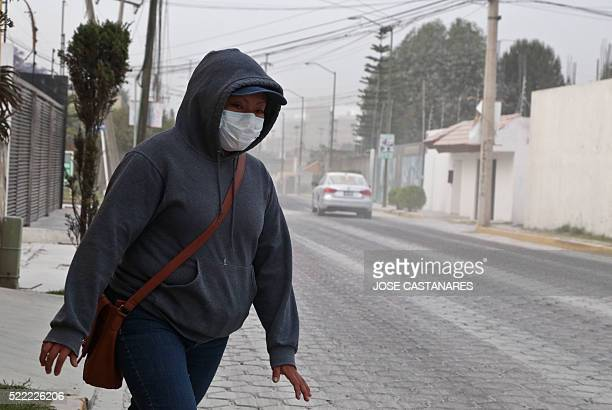 A woman uses a surgical mask to cover from ashes of the Popocatepetl volcano in Puebla Puebla state Mexico on April 18 2016 The activity of the...