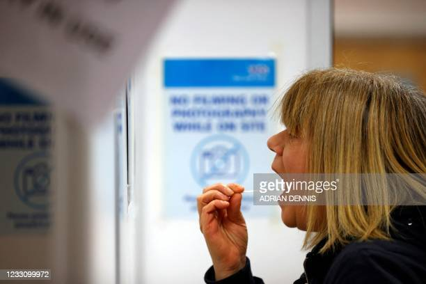 Woman uses a swab to take a sample from her mouth at a NHS Test and Trace Covid-19 testing unit at the Civic Centre in Uxbridge, Hillingdon, west...