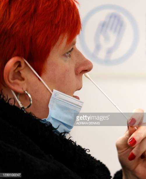 Woman uses a swab to take a sample from her nostril at a NHS Test and Trace Covid-19 testing unit at the Civic Centre in Uxbridge, Hillingdon, west...