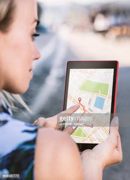 a woman uses a tablet computer to find her way using gps - gps map stock photos and pictures