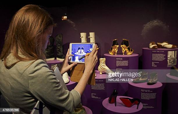 A woman uses a tablet computer to photograph a pair of gold shoes created by British designer Alexander McQueen during a photocall for an exhibition...