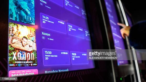 A woman uses a ticket machine displaying an advertisement for the movie Serf on its screen at a cinema in Moscow on February 4 2020 Since its release...
