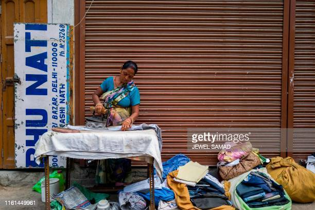 TOPSHOT A woman uses a traditional coal iron to press her customers' clothes in front of a closed store in New Delhi on August 13 2019