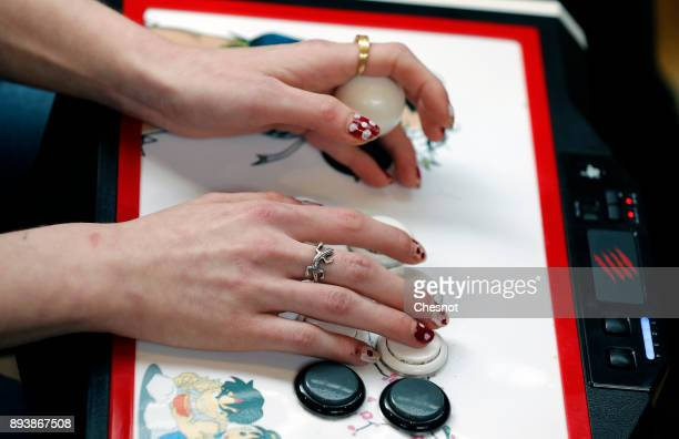 A woman uses a video game controller called an 'arcade stick' as she competes during an esports tournament organized by FDJ at 'Le Carreau du Temple'...