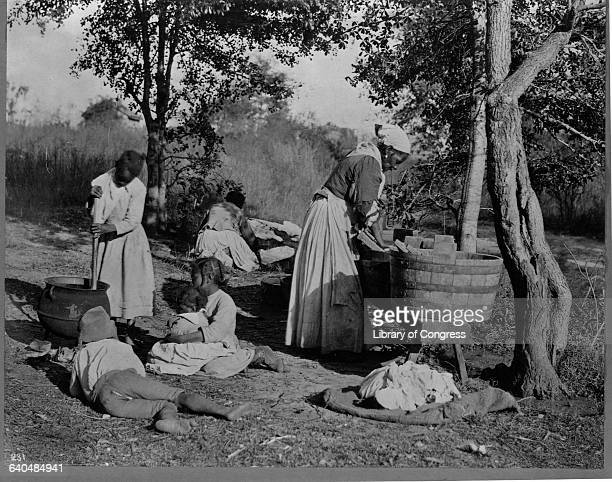 A woman uses a washboard and basin to scrub clothes as a young girl stirs a kettle and another woman spreads laundry out to dry behind them