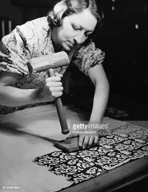 A woman uses a wooden printing block to create a design on cotton cloth