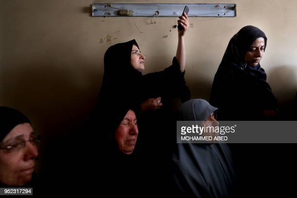 TOPSHOT A woman uses aher cell phone to take pictures during the funeral of 21yearold Palestinian Mohammed AlMaqidin in Gaza city central Gaza Strip...