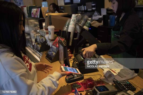 A woman uses an Apple Iphone to pay for her coffee at a Starbucks shop in Beijing on January 3 2019 Apple cut its revenue outlook for the latest...