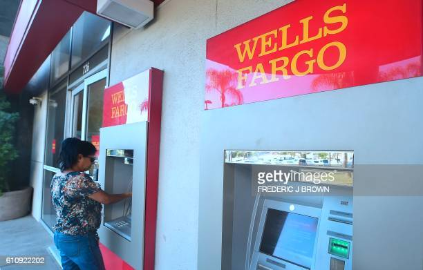 A woman uses an ATM at a branch of Wells Fargo in Alhambra California on September 28 2016 Wells Fargo CEO John Stumpf will forgo $41 million in...