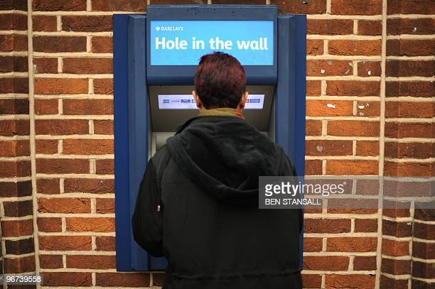 A woman uses an ATM machine at a Barclays bank in south east London on February 16 2010 Barclays on Tuesday said that net profits at the British bank...
