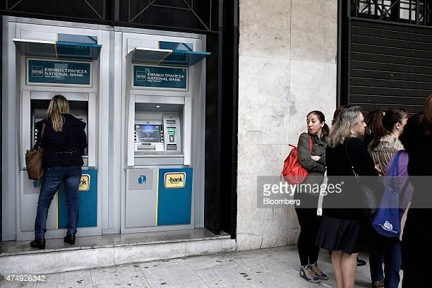 A woman uses an automated teller machine as customers queue outside a National Bank of Greece SA bank branch in Thessaloniki Greece on Thursday May...