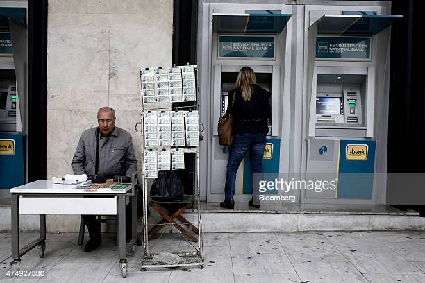 A woman uses an automated teller machine outside a National Bank of Greece SA bank branch as a lottery seller waits for customers in Thessaloniki...