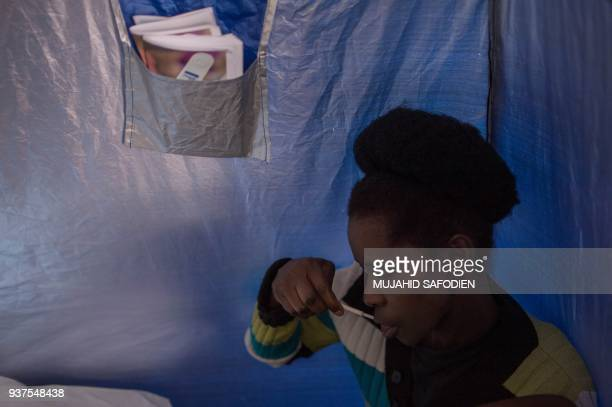 A woman uses an HIV selftesting kit administered by students from the University of the Witwatersrand in Hillbrow Johannesburg on March 19 2018...