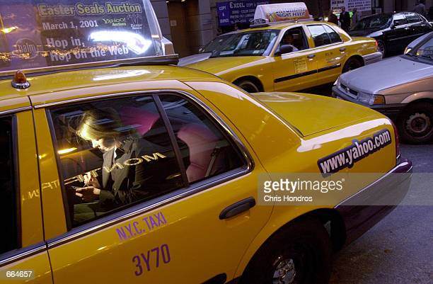 A woman uses an Intenetenabled PalmPilot in the back of a taxi October 2 2000 in New York City Yahoo and Medallion Financial a New York finance...